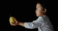Child offering a pear.